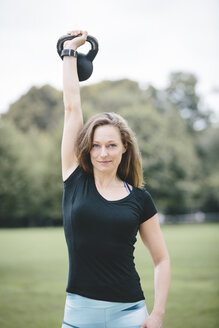 Woman lifting kettlebell in park - MADF000530
