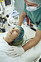 Operating nurse soothing patient on table in operating room - MFF002352