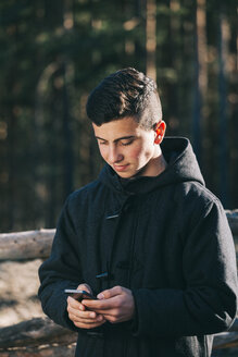 Teenage boy wearing black coat texting on his mobile phone - BZF000267