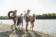 Friends with inner tubes and guitar walking at the riverside - UUF005849