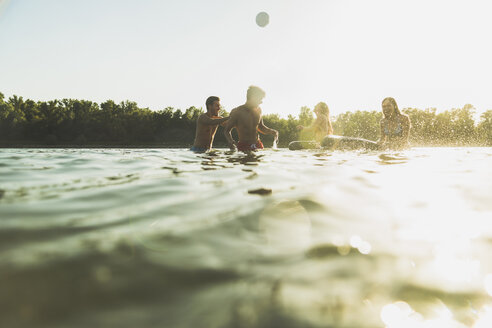 Happy friends with inner tubes and ball in water - UUF005885