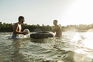 Two friends with inner tube and ball in water - UUF005888