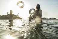 Happy friends throwing inner tubes in water - UUF005891