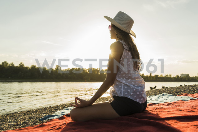 Young woman practicing yoga at the riverside at sunset - UUF005900