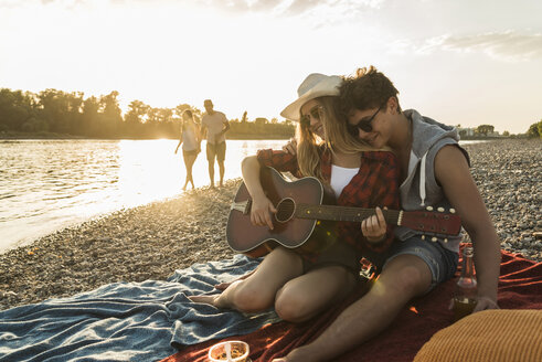 Young couple with guitar relaxing at the riverside at sunset - UUF005912