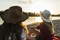 Two friends wearing straw hats relaxing at the riverside at sunset - UUF005918