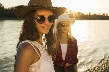 Two friends wearing straw hats and sunglasses at the riverside at sunset - UUF005921