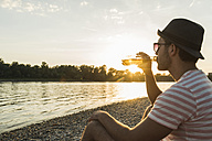 Young man drinking beer at the riverside at sunset - UUF005927