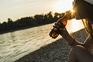 Young woman drinking beer at the riverside at sunset - UUF005930