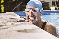 Female triathlete smiling happily at pool's edge - MFF002397