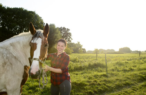 Young woman standing in field, holding her horse - BFRF001553