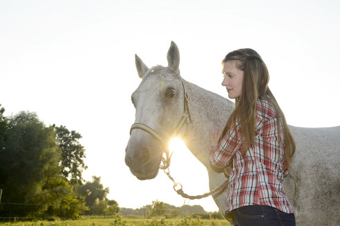 Young woman standing in field, holding her horse - BFRF001556