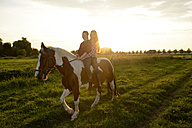Young women riding in field at sunset - BFRF001568