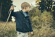 Little boy exploring forest, walking in grass with his stick - MFF002438