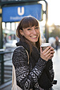 Germany, Berlin, portrait of happy young woman with coffee to go - FKF001399