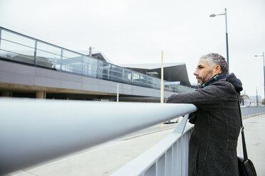 Austria, Vienna, man leaning on a railing near central station - AIF000107