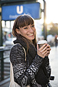 Germany, Berlin, smiling young woman with coffee to go - FKF001405