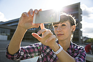 Germany, Berlin, portrait of young woman taking a selfie with smartphone - FKF001414