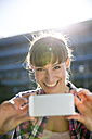Portrait of smiling young woman photographing with smartphone - FKF001426