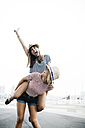 Spain, Barcelona, young woman giving her friend a piggyback ride - JRFF000144