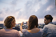 Spain, Barcelona, back view of three friends taking a picture of view with smartphone - JRFF000153