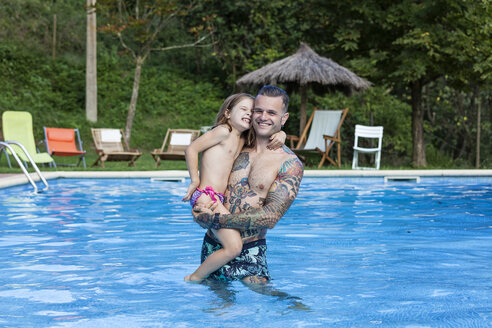 Spain, Girona, tattooed man with his  daughter in a swimming pool - XCF000039