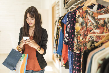 Young woman in fashion boutique using smart phone - JASF000201