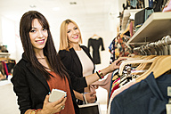 Young women in fashion boutique shopping for clothes - JASF000204
