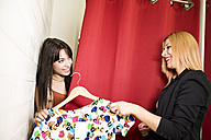 Young woman in fashion boutique trying on dress, friend helping - JASF000216