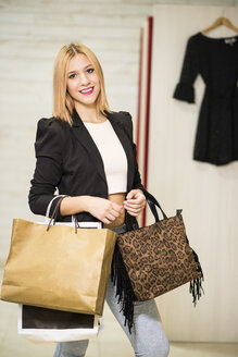 Young woman in fashion boutique carrying shopping bags - JASF000228