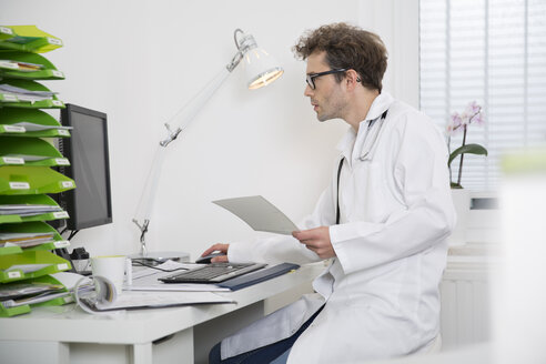 Doctor sitting at desk working on computer - FKF001440