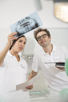 Two dentists in dental surgery discussing x-ray image - FKF001458