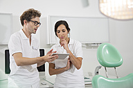 Two dentists in dental surgery with digital tablet discussing - FKF001461
