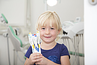 Girl in dental sugery holding toothbrushes - FKF001467