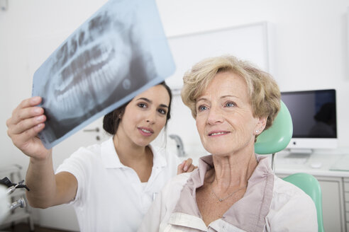 Dentist explaining x-ray image to senior woman in dentist's chair - FKF001479