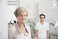 Portrait of smiling senior woman in surgery with dentist in background - FKF001485