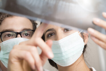 Two doctors with mouth masks looking at x-ray image - FKF001512