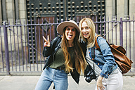 Spain, Barcelona, two playful young women in front of entrance portal - EBSF000935