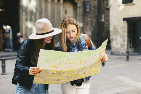 Spain, Barcelona, two young women reading map - EBS000941