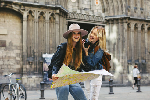 Spain, Barcelona, two happy young women with camera and map - EBS000944