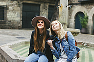Spain, Barcelona, two young women sitting at a fountain looking up - EBSF000947