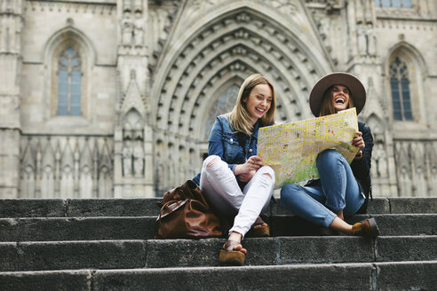 Spain, Barcelona, two happy young women reading map on stairs - EBS000956