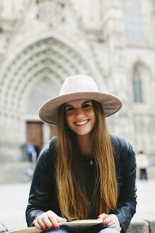 Spain, Barcelona, portrait of smiling young woman with map - EBSF000959