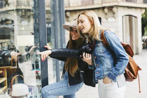 Two young women looking in shop window - EBSF000965