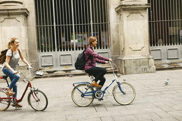 Spain, Barcelona, two young women riding bicycle in the city - EBSF000968