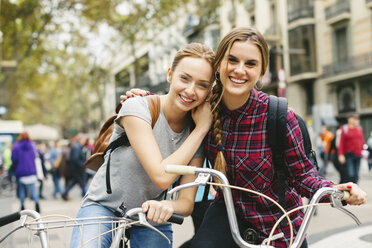 Spain, Barcelona, two young women on bicycles in the city - EBSF000971