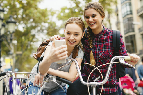 Spain, Barcelona, two young women with cell phone and bicycles in the city - EBSF000974