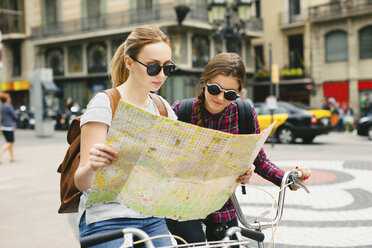 Spain, Barcelona, two young women with map on bicycles in the city - EBS000977