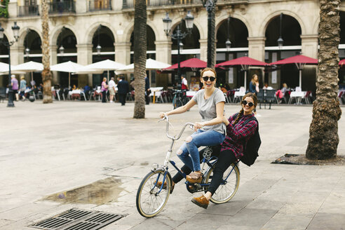 Spain, Barcelona, two happy young women sharing bicycle in the city - EBSF000980