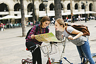 Spain, Barcelona, two happy young women with map on bicycles in the city - EBS000983